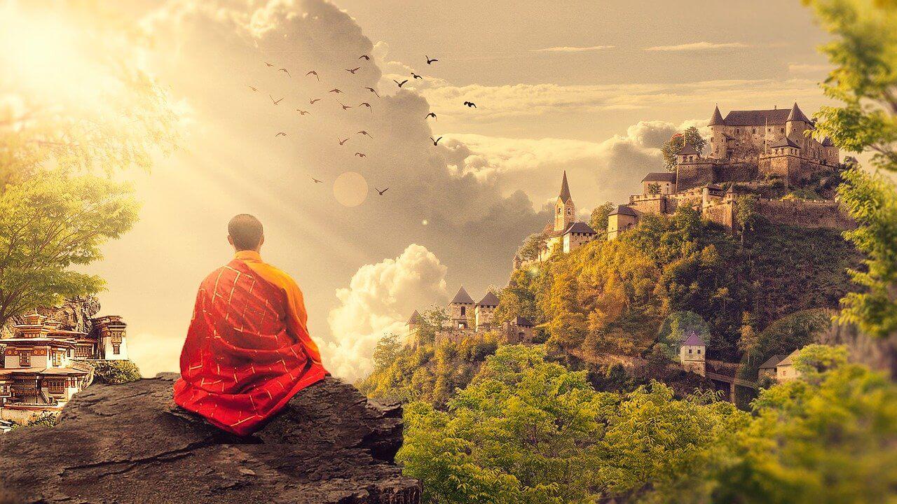 mantras indianos: monge budista contemplando uma paisagem iluminada, colorida e com muita natureza.