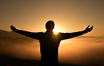 Homem-com-os-braços-abertos-em-direção-ao-pôr-do-sol