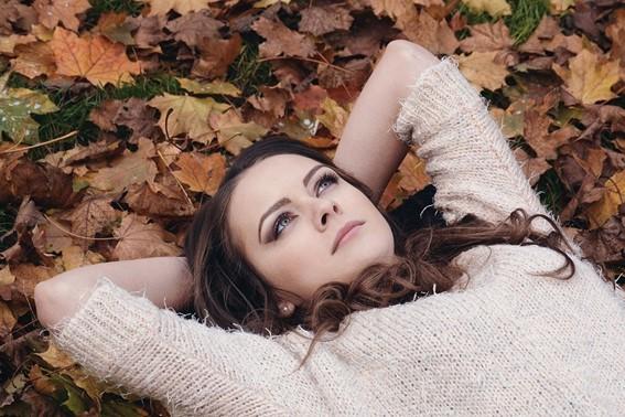 mulher de pele clara e cabelos castanhos deitada sobre folhas secas, com os braços atrás da cabeça e olhar pensativo para o céu.