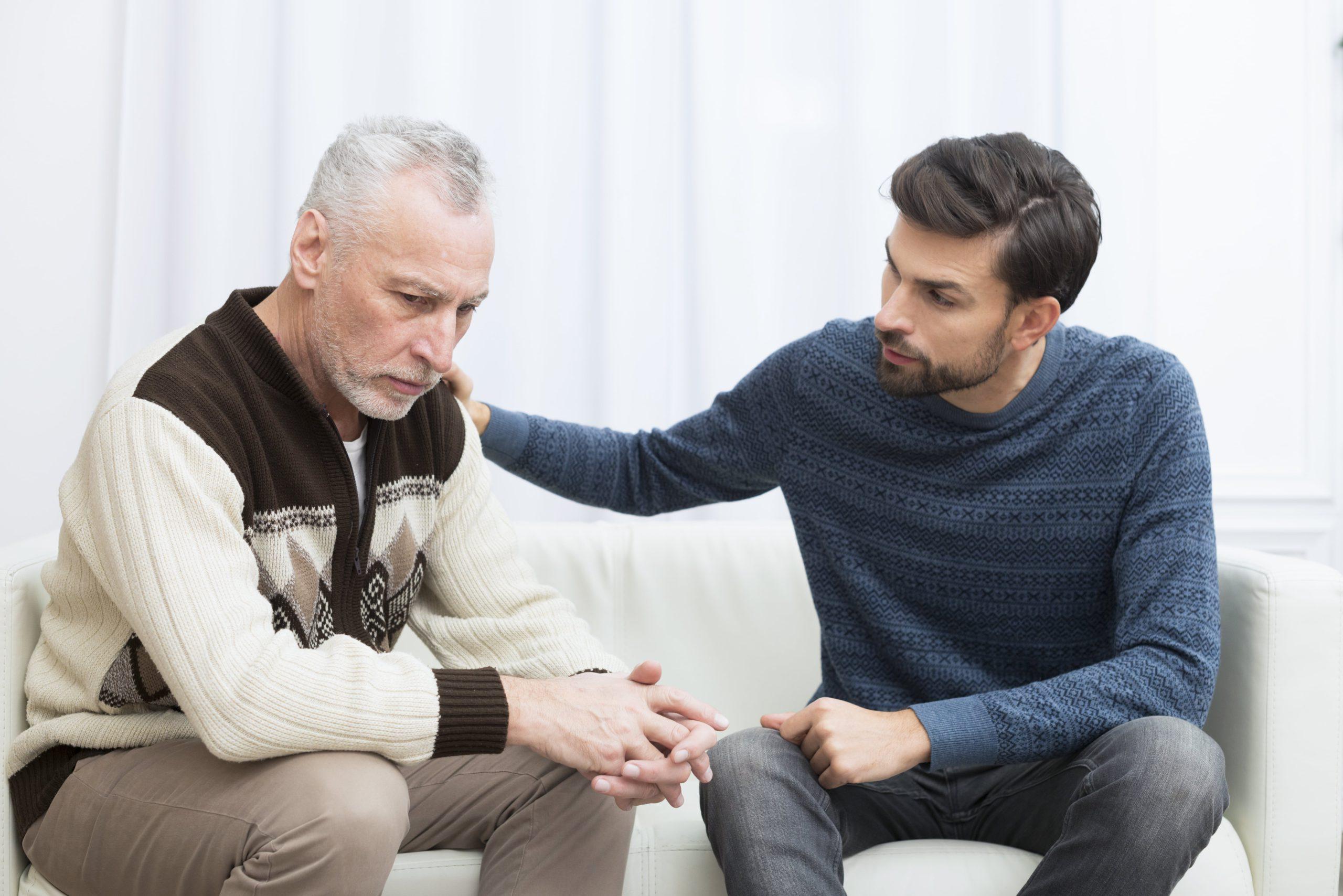 Idoso fica triste durante conversa com homem jovem