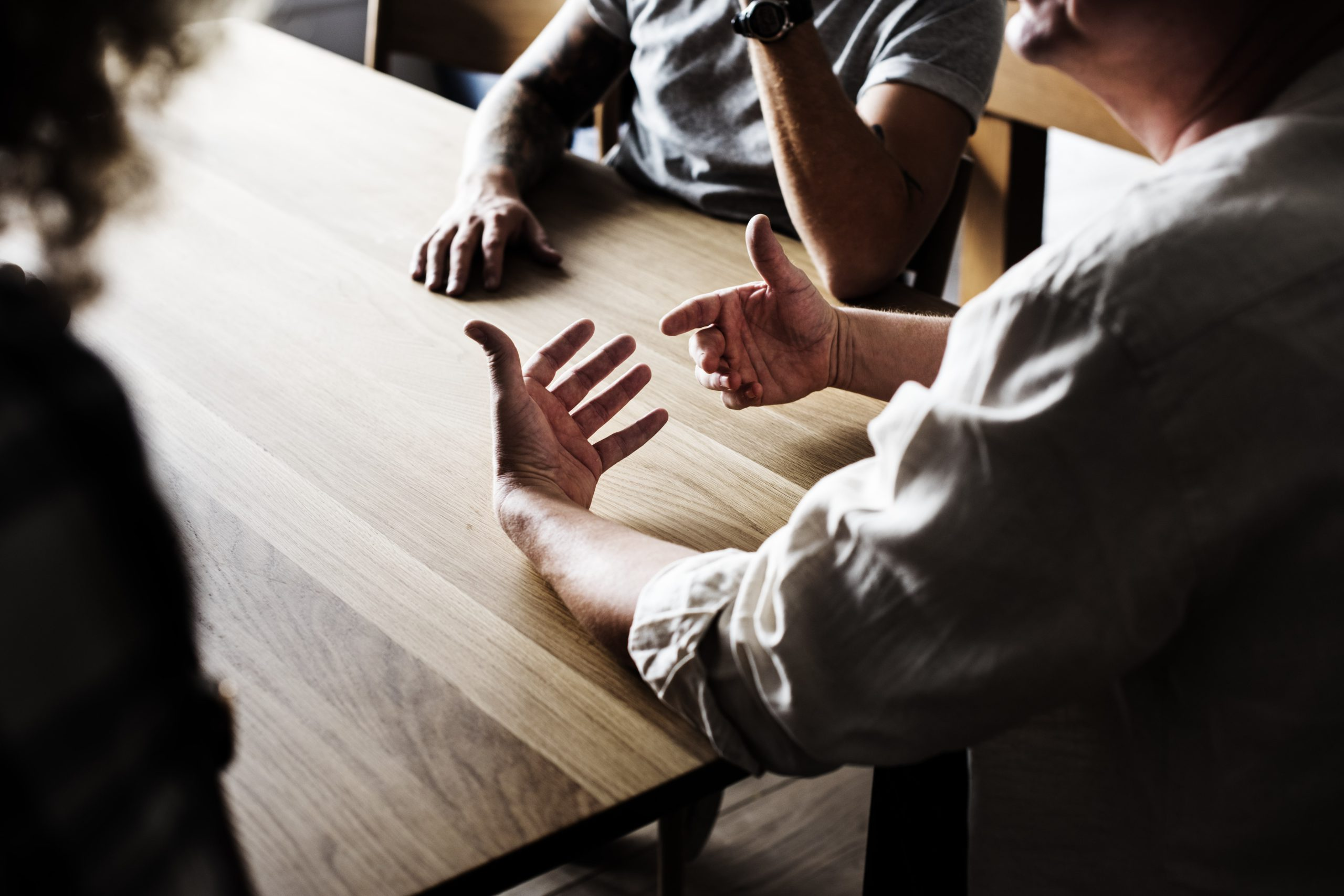 Pessoas conversam em volta de uma mesa