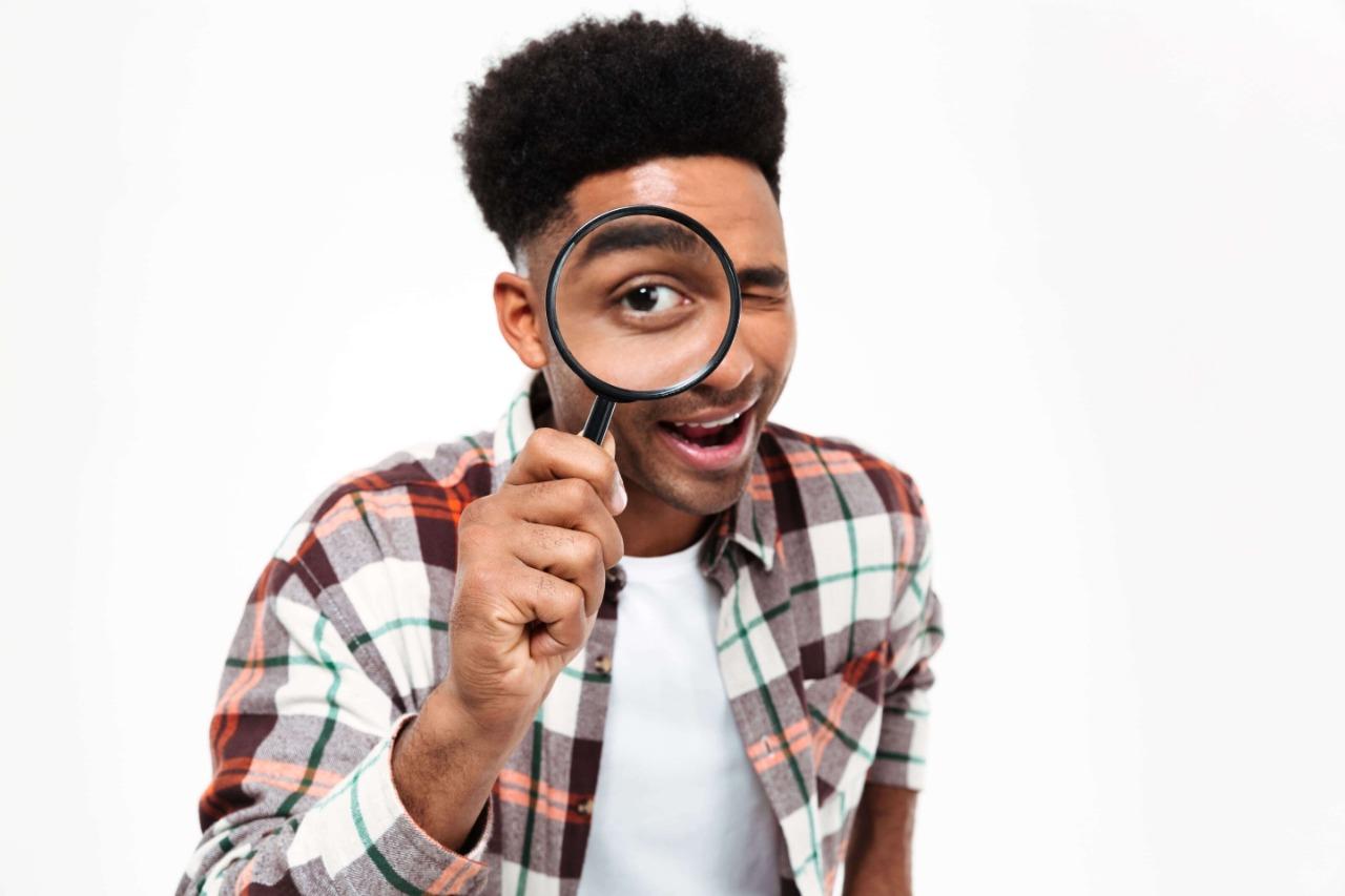 Homem negro usando camisa xadrez, segurando uma lupa na direção do olho esquerdo - como encontrar a sua missão de vida