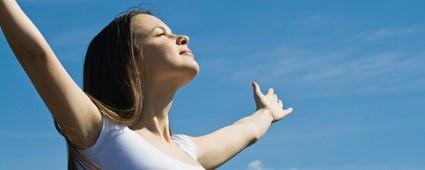 mulher de pele clara, cabelos castanhos lisos e longos, de braços abertos, olhos fechados e cabeça voltada para o céu azul.