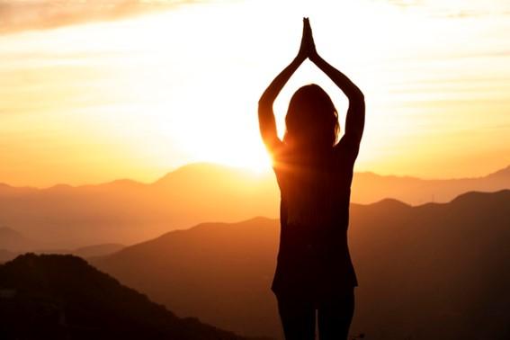 mulher de frente para o sol, com as mãos unidas em formato de oração acima da cabeça.