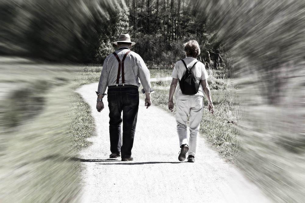 foto em preto e branco de jovem e idoso andando pela rua