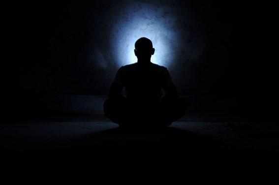 silhueta de um homem sentado em posição de lótus no escuro com um foco de luz branca e azul em direção à cabeça.