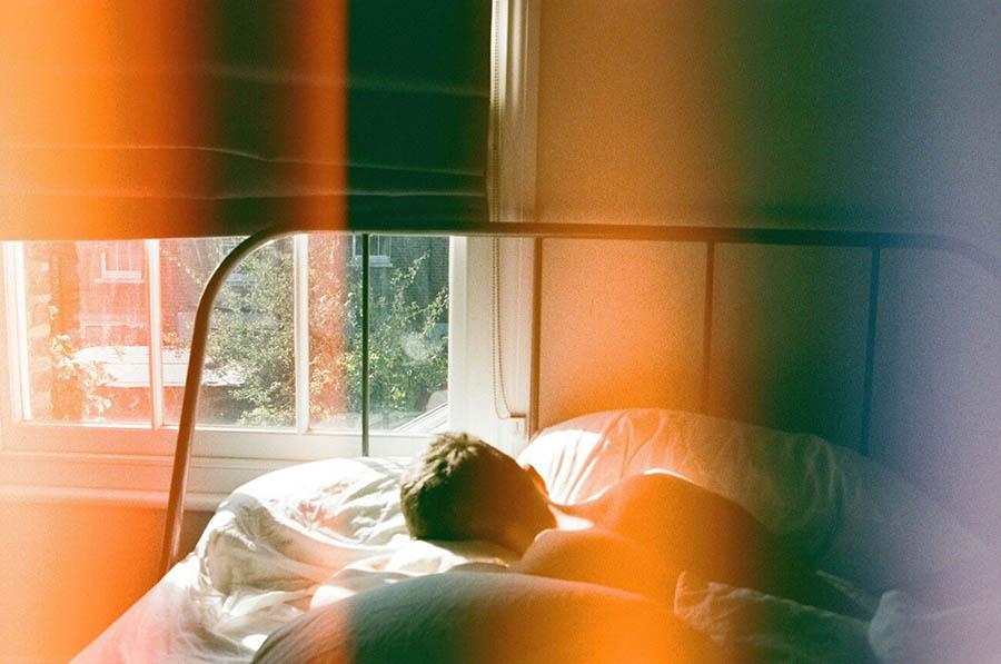 pessoa embaixo das cobertas, dormindo e uma luz amarelada entrando no quarto