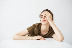 Mulher debruçada na mesa com mão na cabeça expressa fadiga