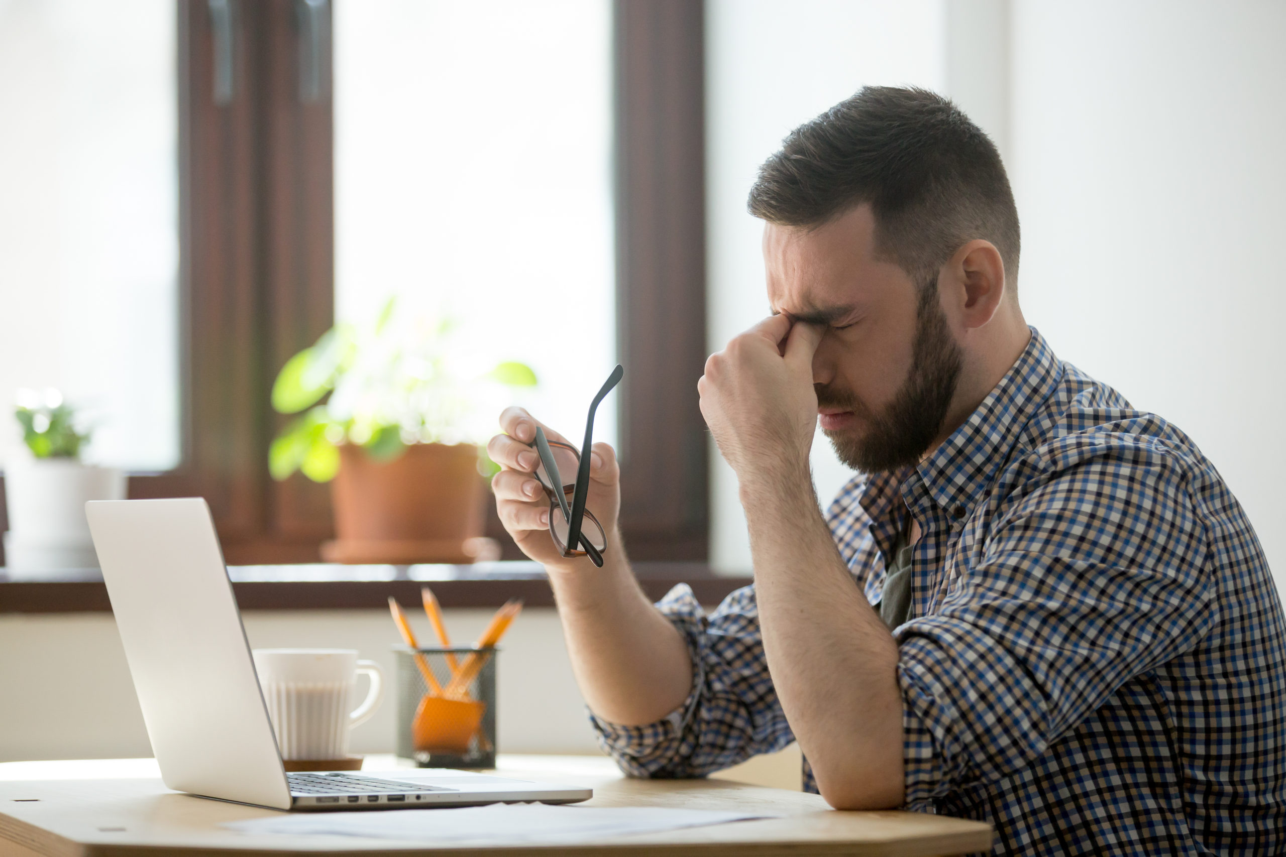 Homem em frente ao computador tira os óculos e coloca mão nos olhos expressando cansaço
