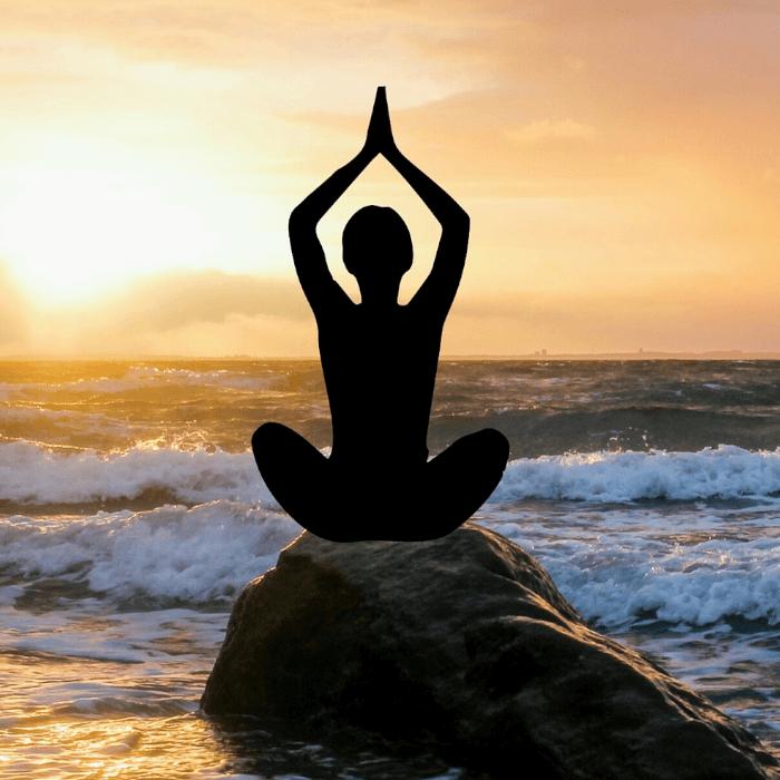 Pessoa medita em cima de uma pedra de frente ao mar