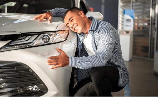 Homem abraça carro novo em concessionária