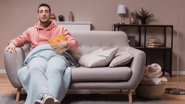 5 Programas de TV que roubam seu dinheiro - homem sentado no sofá come pipoca e assiste tv