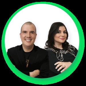 Bruno Gimenes vestido com roupas pretas à esquerda e Patrícia Cândido à direita com roupas pretas. Ambos sorriem e estão com os braços cruzados em frente ao peito.
