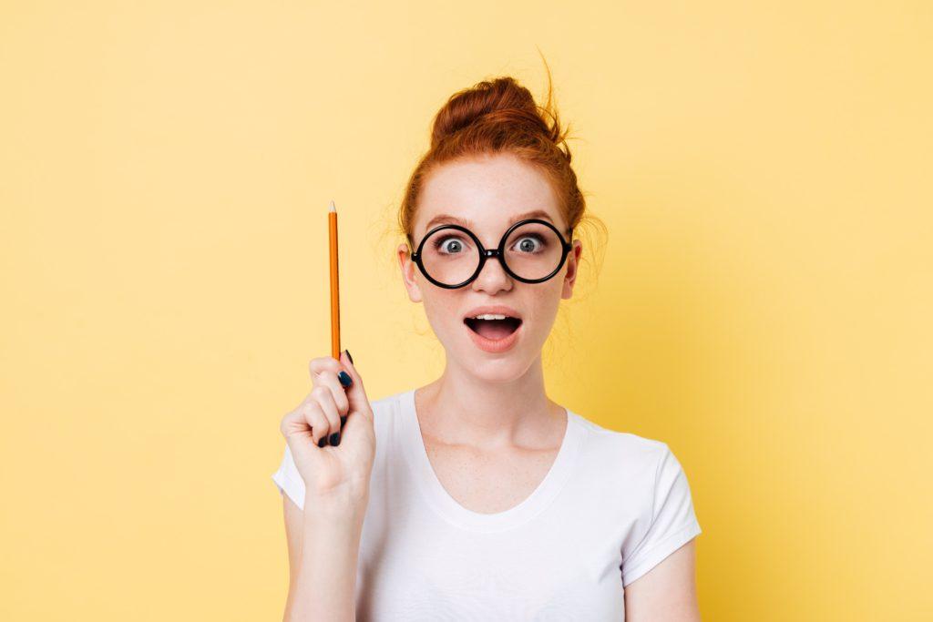 Mulher ruiva de óculos e lápis na mão com expressão que teve uma ideia