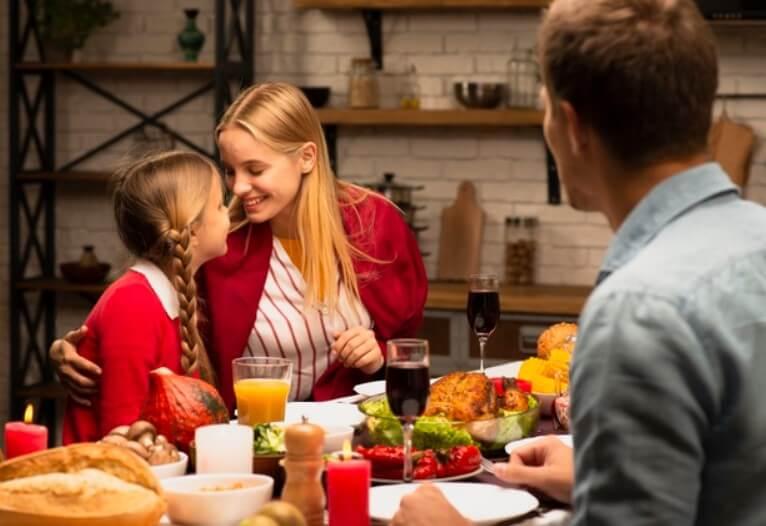 Pai, mãe e filha comendo à mesa farta