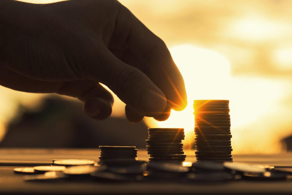 Aura Money mão acrescentando moeda em uma pilha de moedas douradas