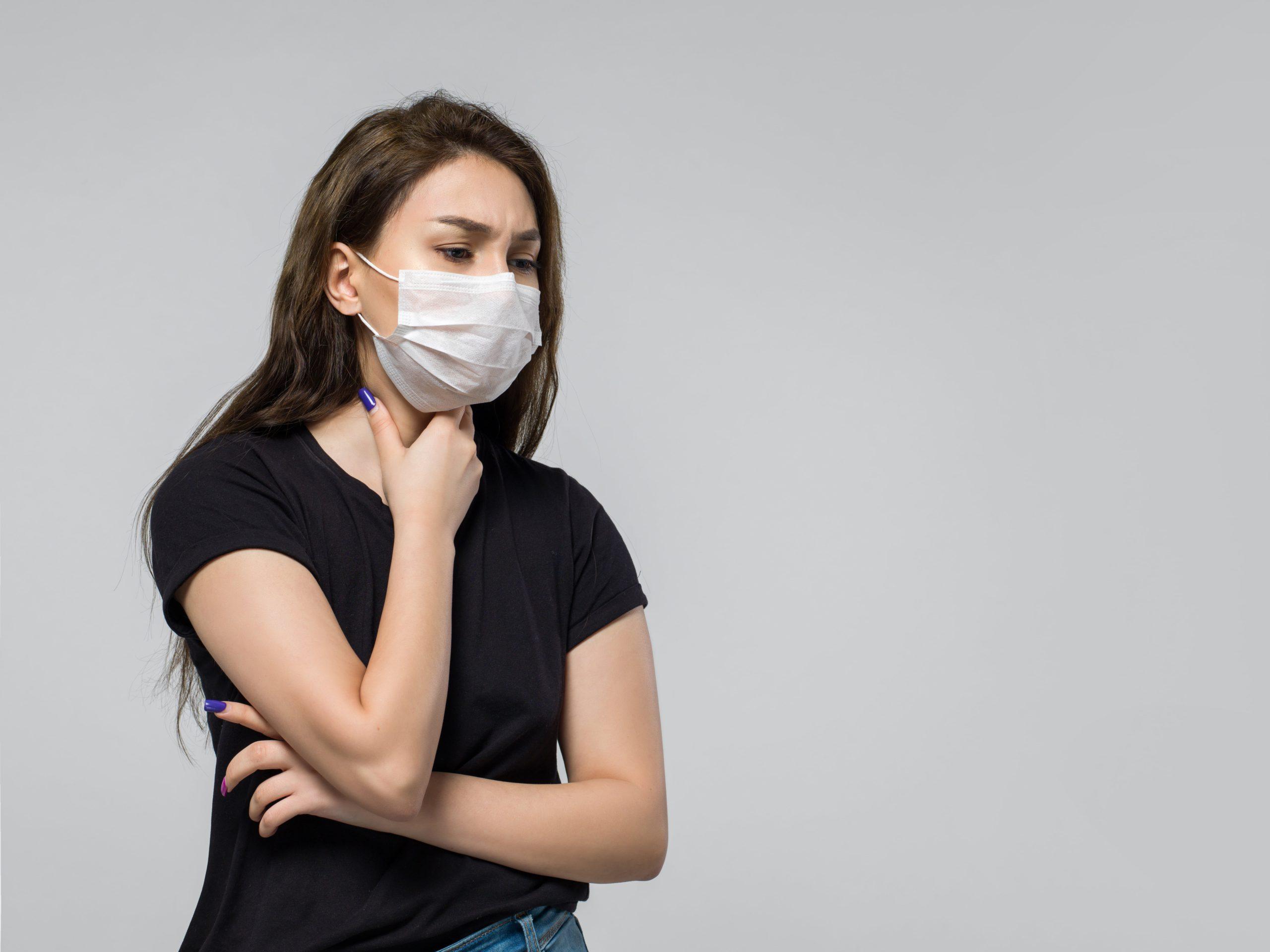Mulher com máscara colocando a mão de garganta com expressão de dor
