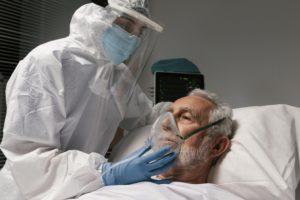 Idoso doente na cama do hospital sendo cuidado por um profissional de saúde