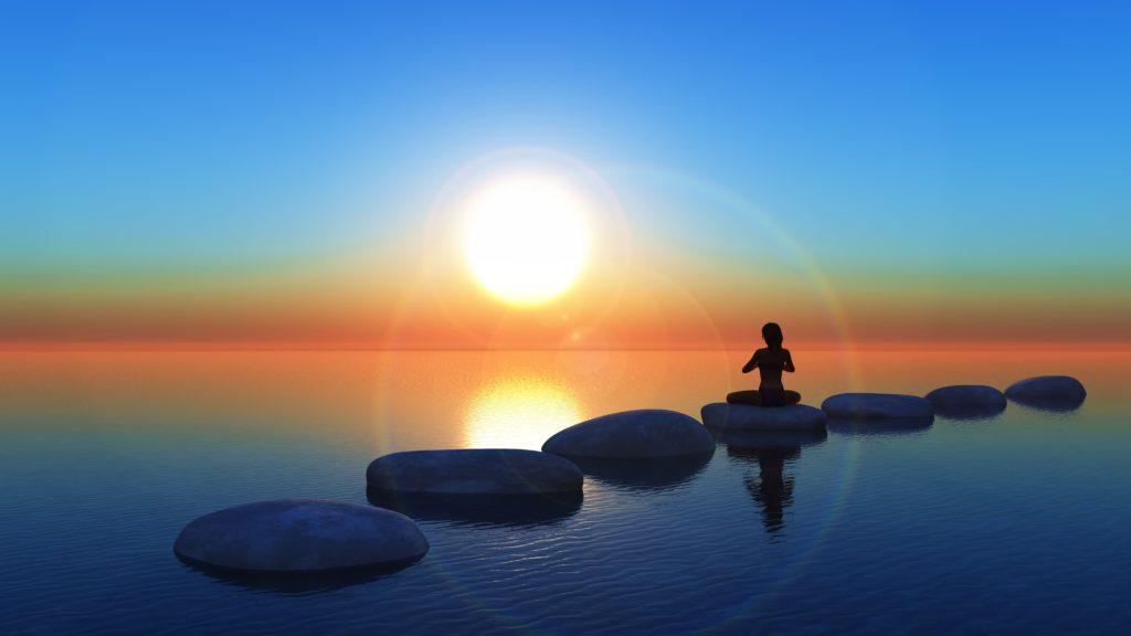 Paisagem com uma mulher meditando sob o pôr do sol em cima de pedras em um lago. Luz da Serra