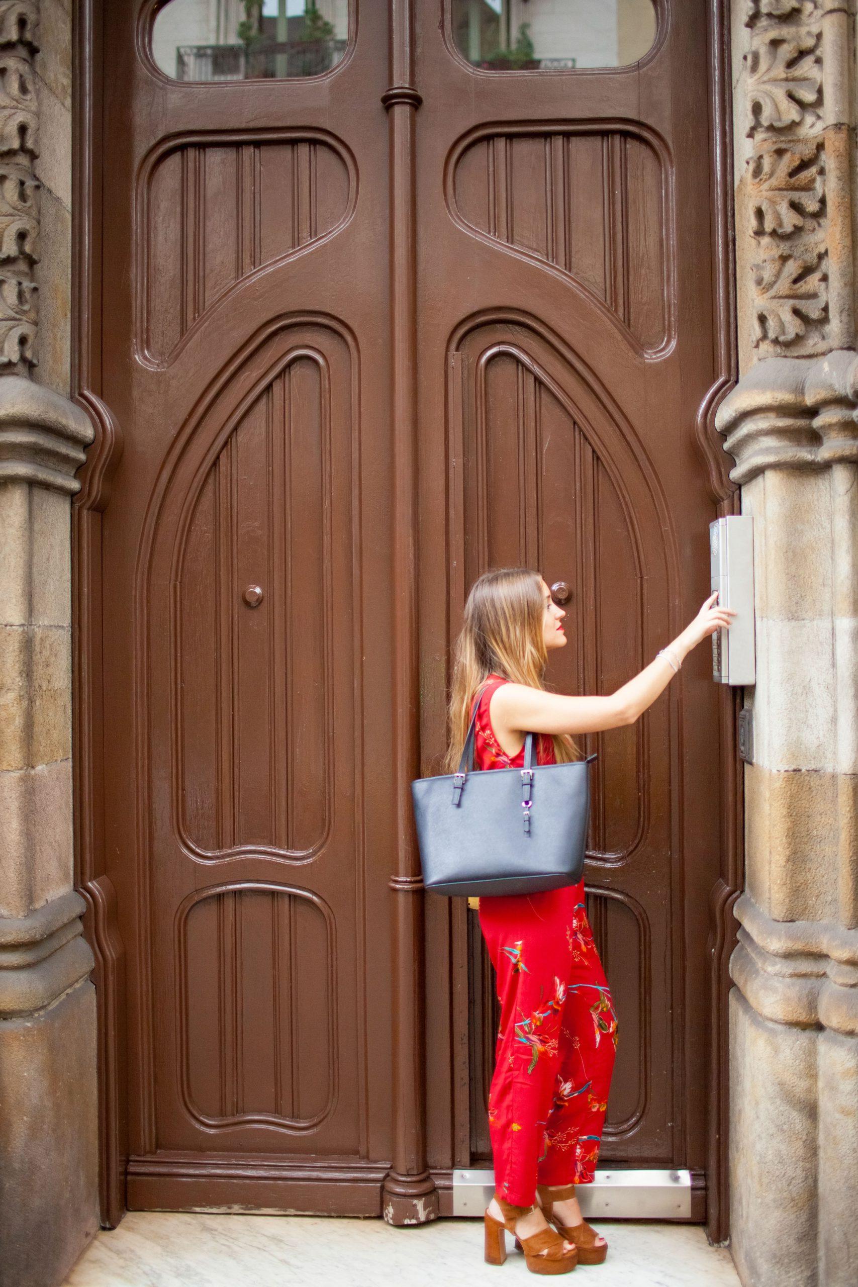 Mulher loira toca interfone de casa com porta marrom
