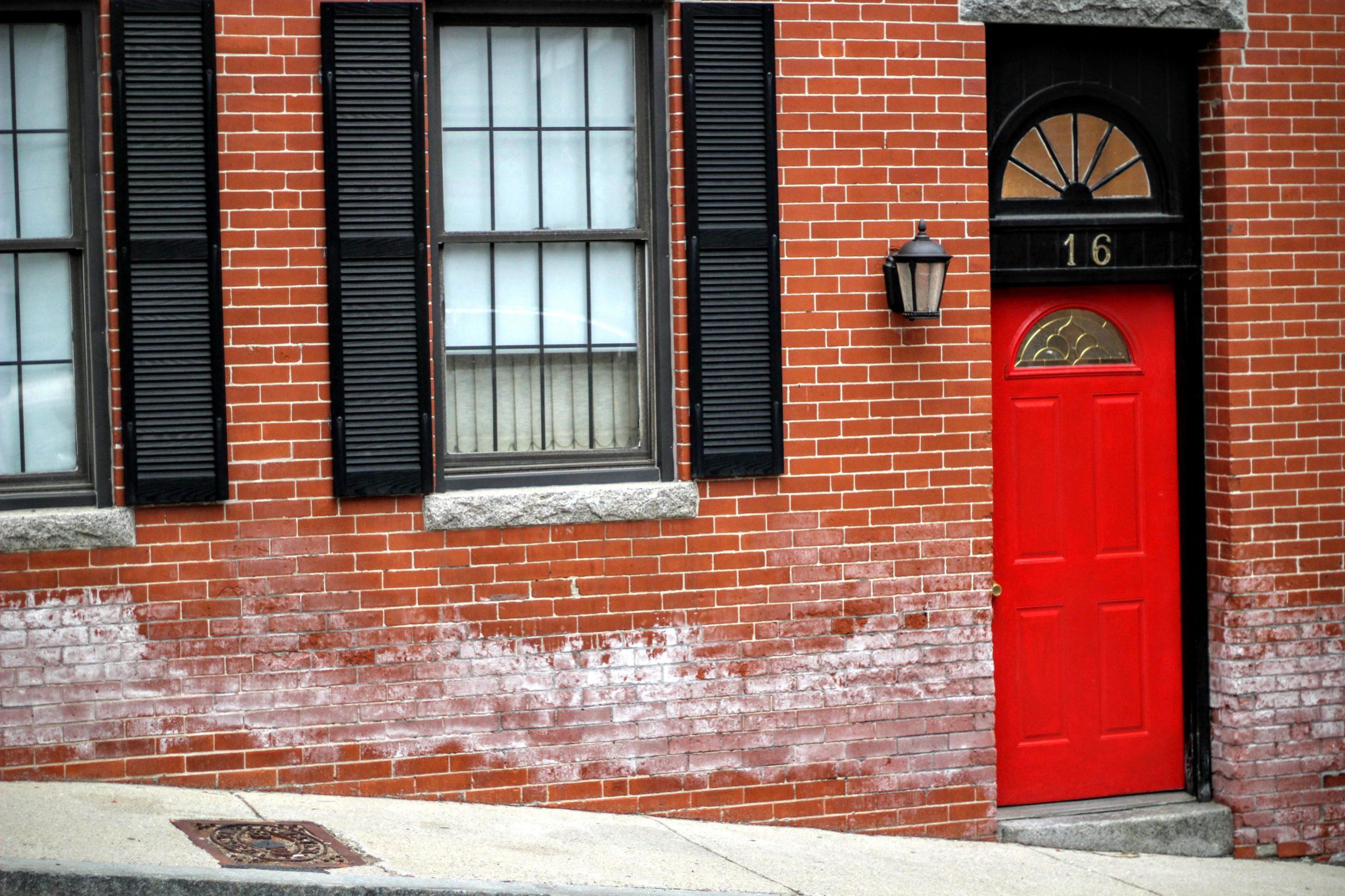 Fachada de habitação com portão vermelho e de número 16