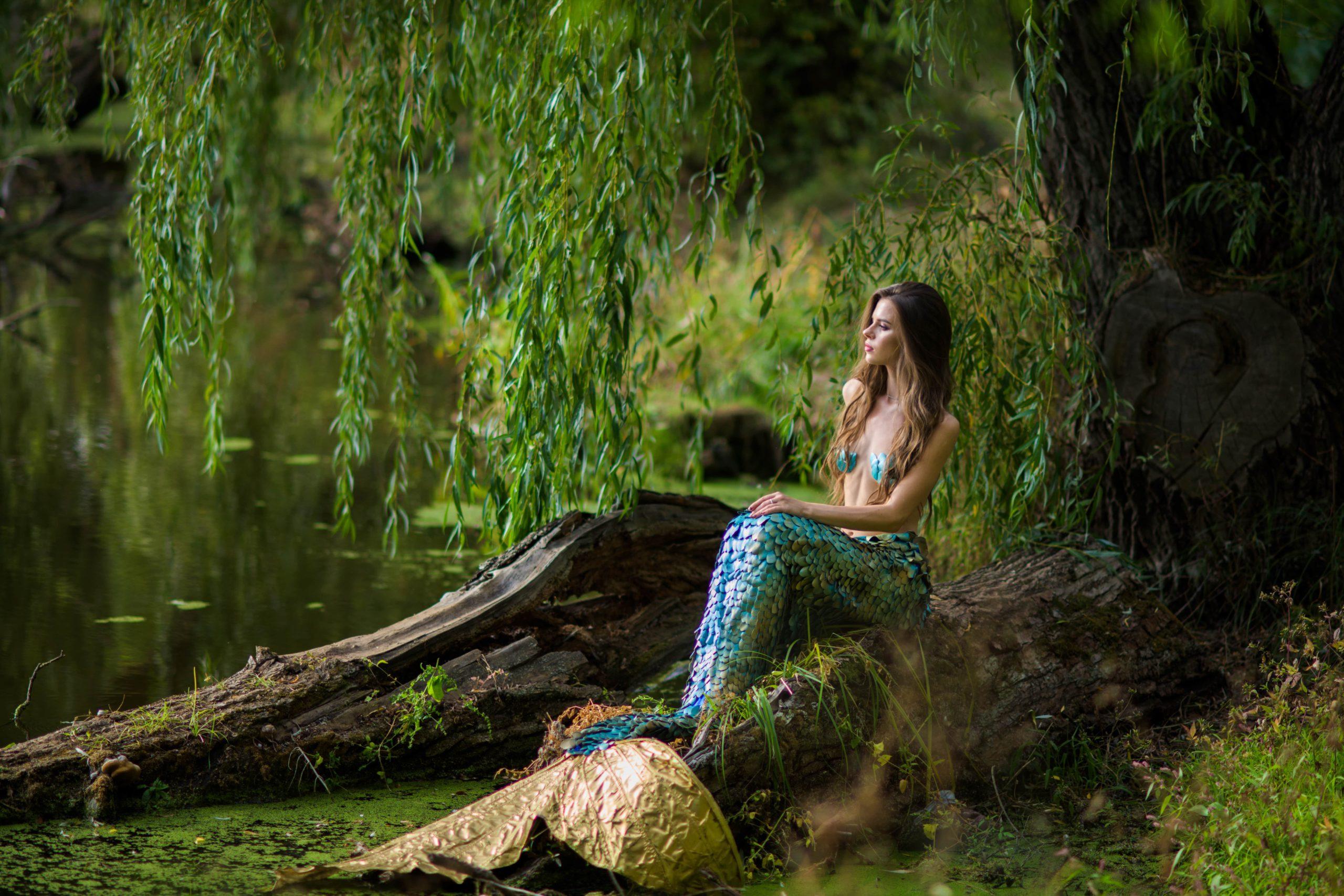 Sereia sentada à beira de um rio