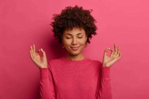 mulher negra com roupa rosa, fazendo sinal de meditação