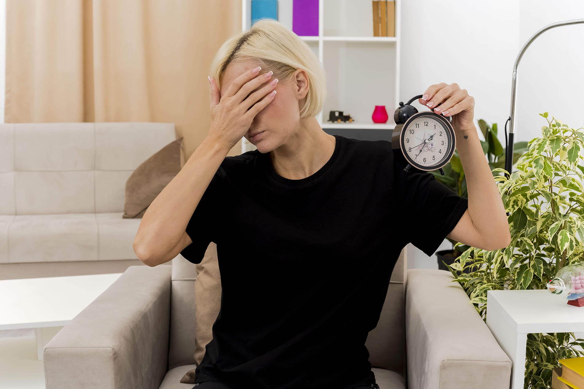 Mulher loira com cabelo curto, com a mão no rosto, não querendo olhar para o relógio que segura na outra mão: mistério de acordar às 3h da manhã – Luz da Serra