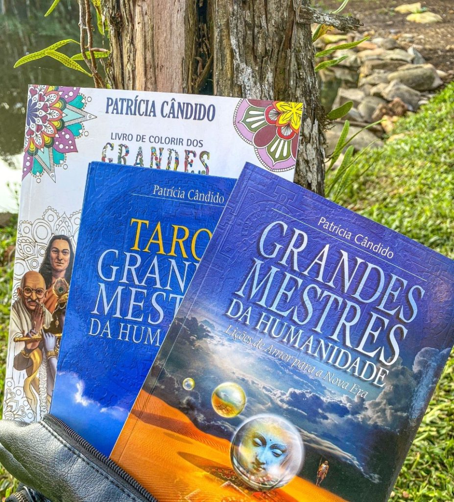 três livros com temáticas espirituais escritos por Patrícia Cândido. Os três estão dispostos em uma bolsa, em um ambiente aberto e ensolarado.