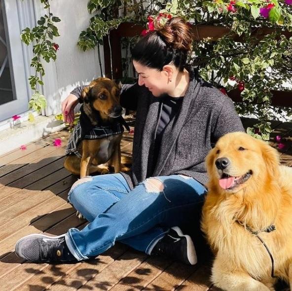 patrícia cândido sentada em uma superfície de madeira com seus dois cachorros de estimação.