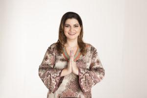 Patrícia Cândido com os braços em frente do peito, fazendo o gesto de namastê.