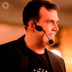 bruno gimenes aparece de perfil, usa uma camisa e blazer pretos e um microfone