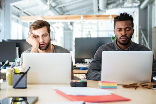 jovens trabalhando no notebook em escritório: um está com fones de ouvido e mão no rosto, já o outro está focado no que está fazendo