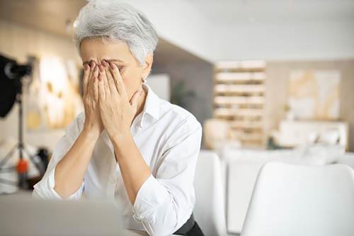 Mulher de cabelos grisalhos escondendo o sofrimento do rosto