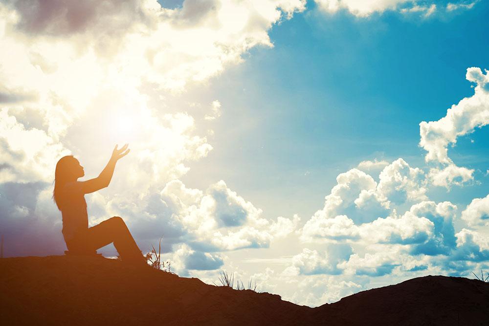 mulher sentada em uma montanha, admirando o céu ensolarado - proteção espiritual e energética
