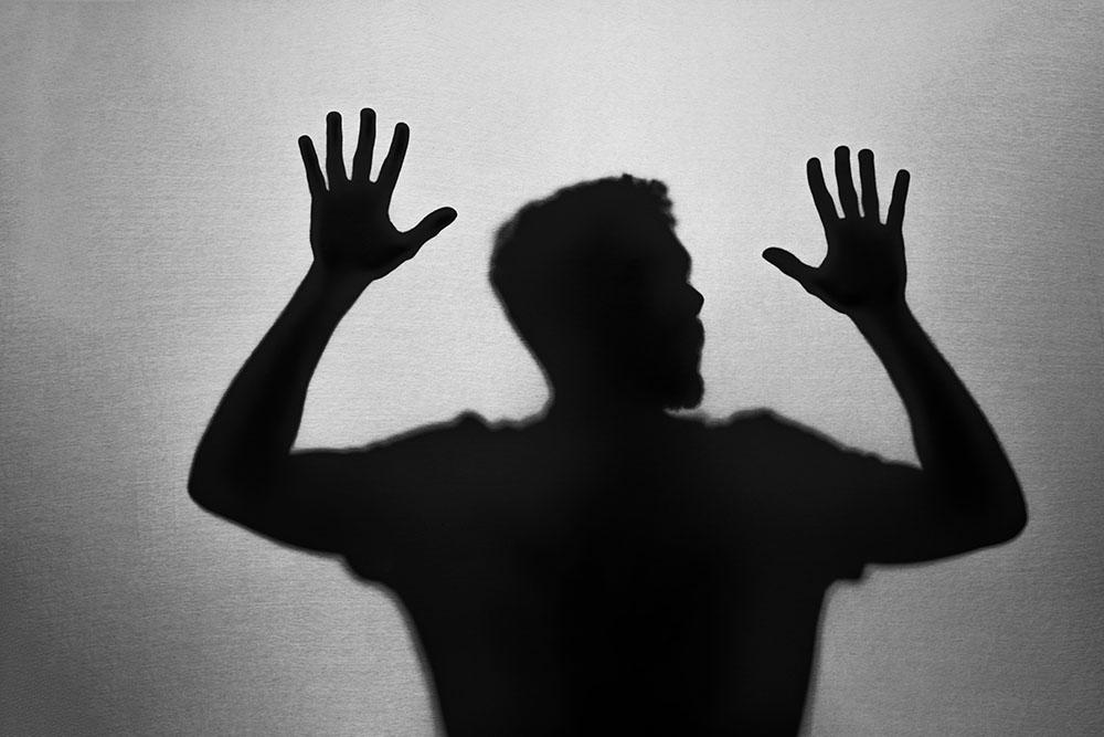 Sombra de um homem com as mãos erguidas, seu corpo está grudado em um vidro – proteção espiritual.