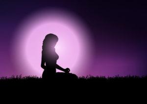 Imagem da silhueta de uma mulher posando em um campo. Sua sombra contrasta com o fundo em tons de roxo e lilás – proteção espiritual e energética.