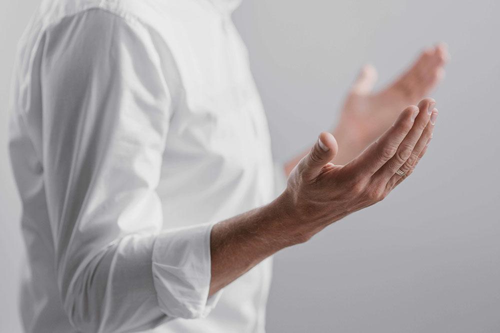 Imagem de perfil de um homem com blusa de mangas compridas branca com os braços esticados, orando. Fitoenergética.