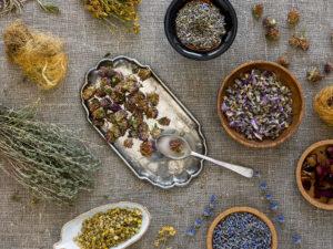 imagem de cima mostrando uma mesa com diversas ervas, como camomila e lavanda. As plantas possuem energia fitoenergética.