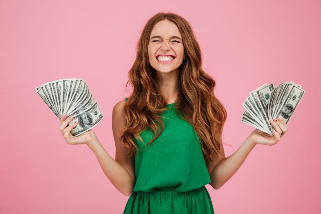 mulher de vestido segurando um leque de dinheiro em cada uma das mãos