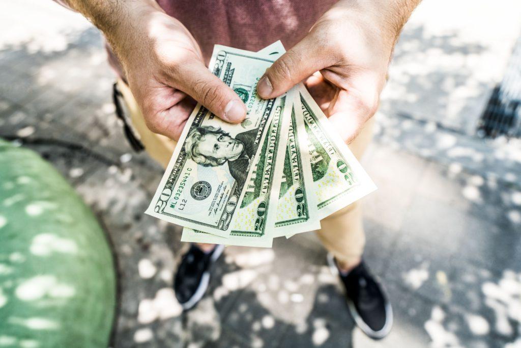 homem em pé na rua segurando um leque de dólares com as duas mãos