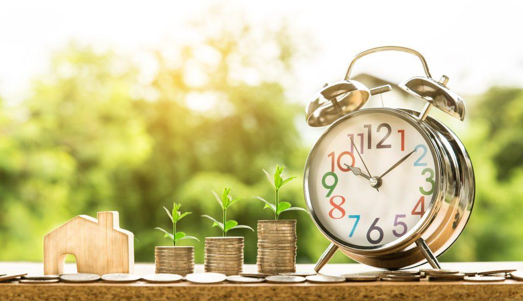 Casa em miniatura, moedas e relógio de mesa lado a lado