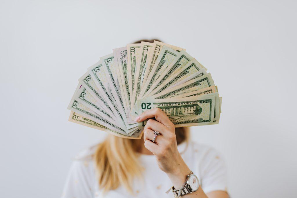Mulher segura leque de dinheiro