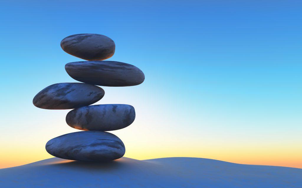 Pedras equilibradas uma em cima da outra com paisagem de por do sol ao fundo