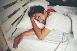 Homem deitado na cama expressa dificuldade para dormir