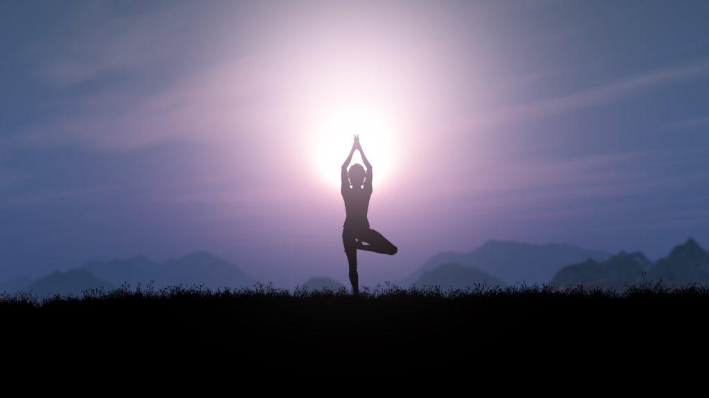 Mulher se alinha à paisagem do pôr do sol ao realizar posição da árvore de ioga